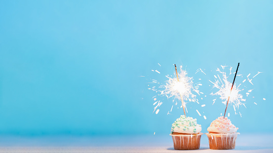 Two cupcakes decorated with colorful sprinkles and sparklers. Festive cupcakes on blue background with copy space left for text or design. Banner