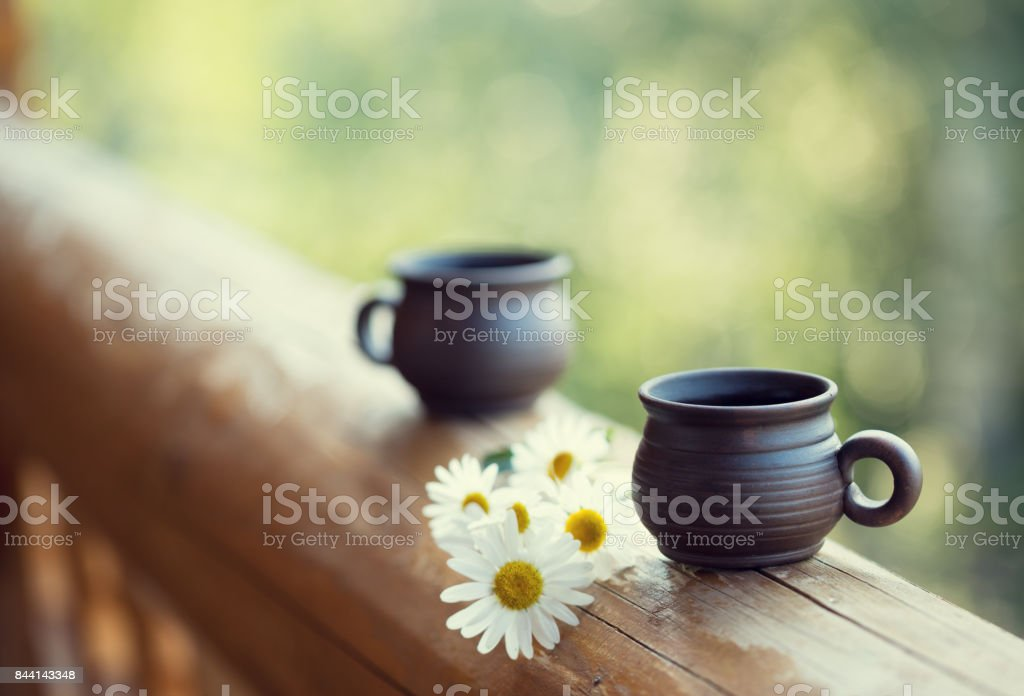 Two cups and bouquet of chamomiles on the railing of the balcony. Toned image stock photo
