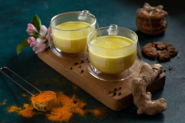 Duas xícaras de ayurvédico bebem leite dourado com leite em pó curcuma, gengibre e mel sobre fundo de textura verde. - foto de acervo