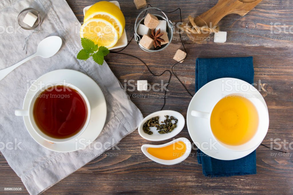 Two cups of black and green tea with cane and white sugar cubes on wooden rustic table with lemon, mint leaves and dried tea leaves, honey. Top view. - foto stock