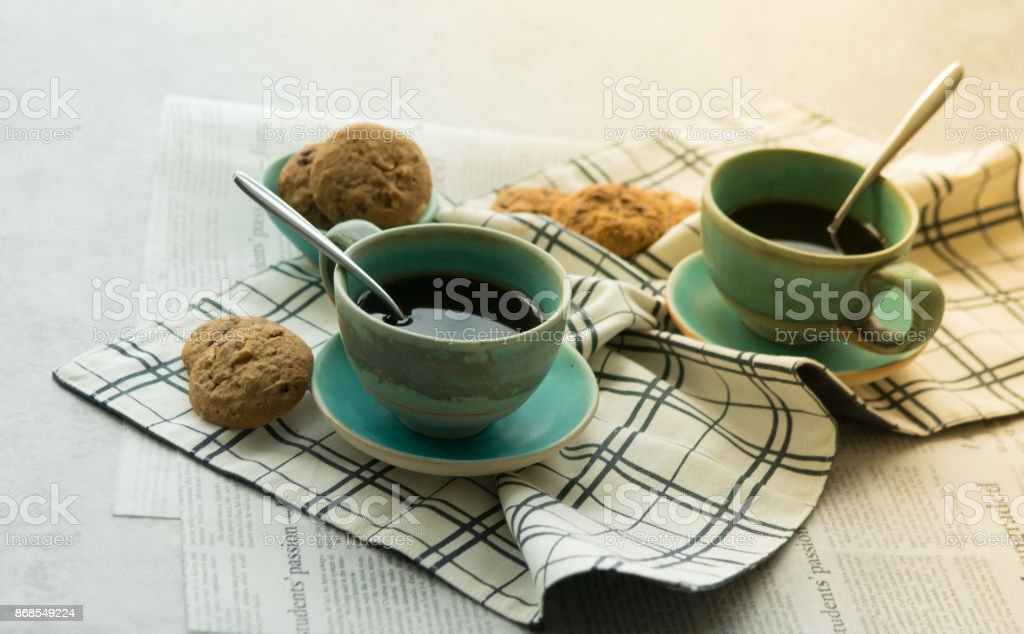 Two cups of black coffee with spoon on supported dish on fabric on black and white newspaper are put on hard table in the early morning with bright yellow light and some biscuits for refresh after wake up. stock photo