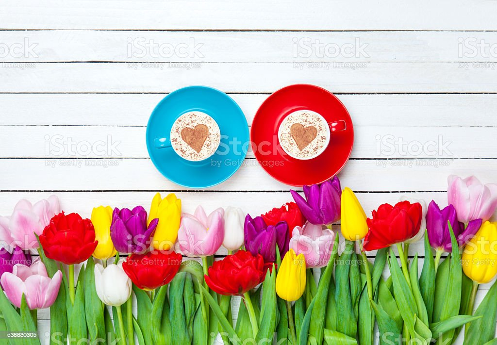 Two cups of Cappuccino and tulips stock photo