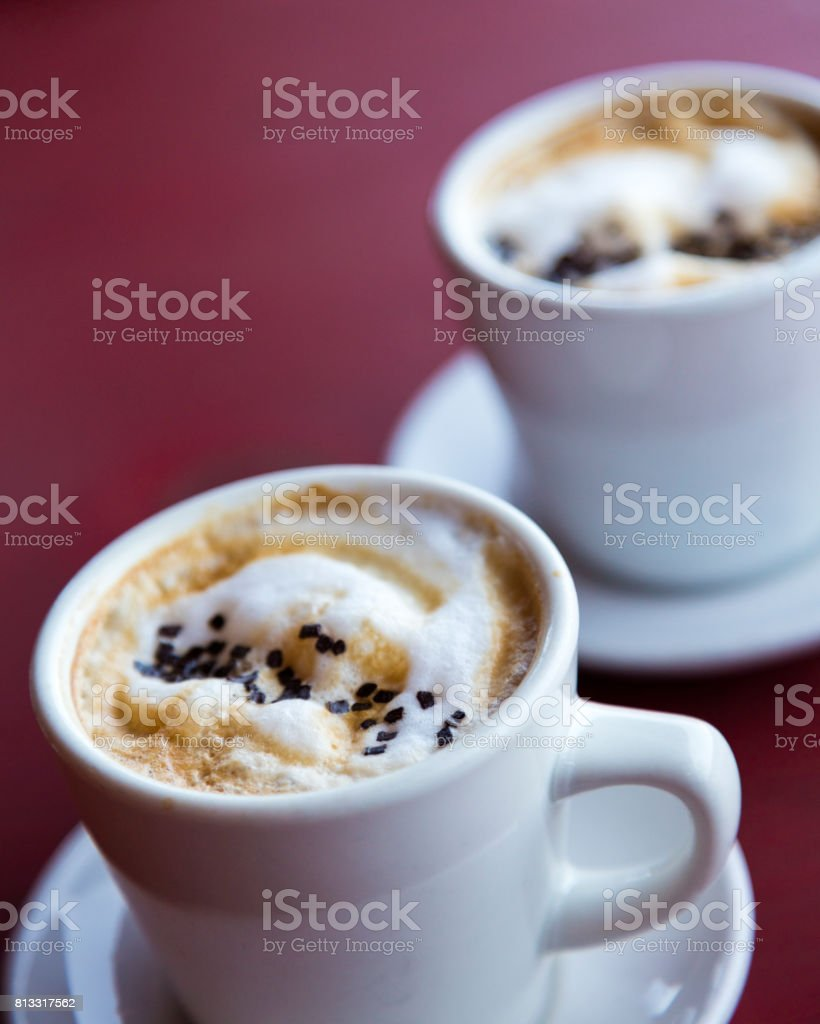 Two cups of cappuccino coffee in white porcelain cups, shot on a red background. stock photo