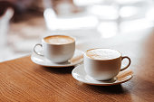Two cups of cappuccino with latte art on wooden desktop