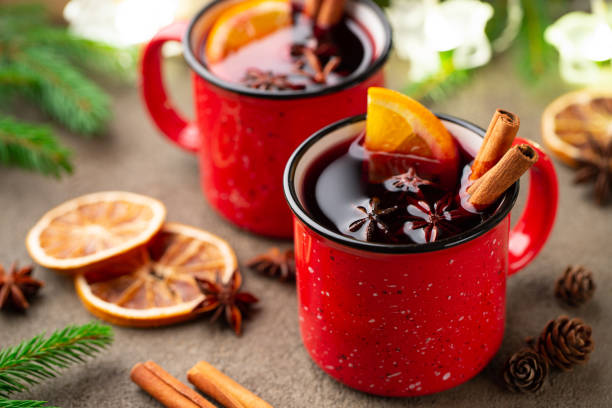 two cups of christmas mulled wine or gluhwein with spices and orange slices on rustic table top view. traditional drink on winter holiday - mulled wine stock photos and pictures
