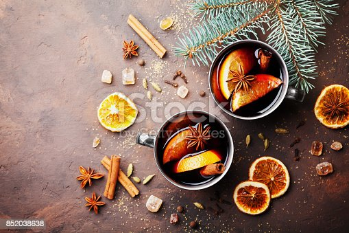 istock Two cups of christmas mulled wine or gluhwein with spices and orange slices on rustic table top view. Traditional drink on winter holiday. 852038638