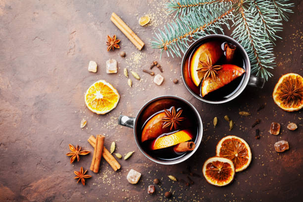 Two cups of christmas mulled wine or gluhwein with spices and orange slices on rustic table top view. Traditional drink on winter holiday. stock photo