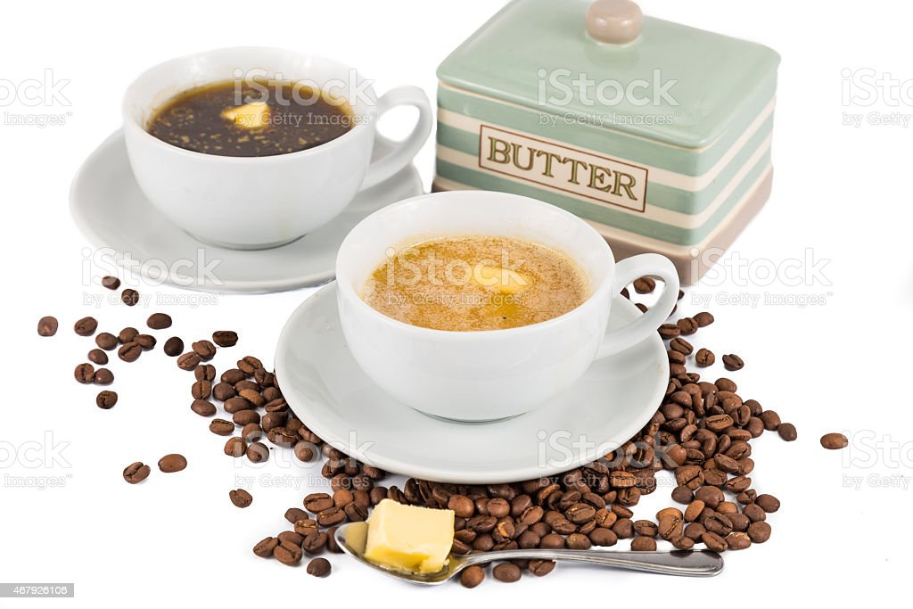 Two cups of coffee and butter, one black and one with milk stock photo
