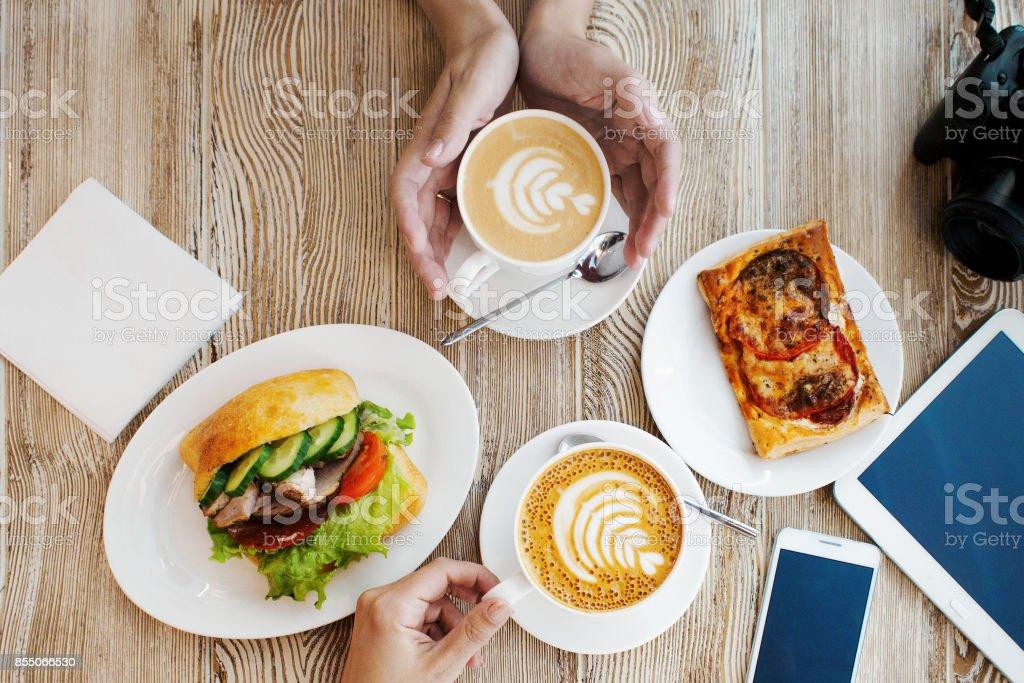 Dos tazas de café, agradable ambiente. Sándwich de pollo, taza de café y smartphone sobre la mesa - foto de stock