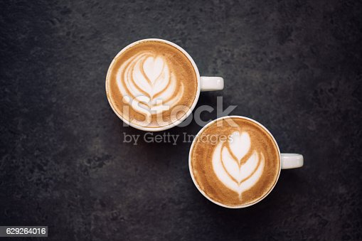 istock Two cups of coffee on black rustic background 629264016