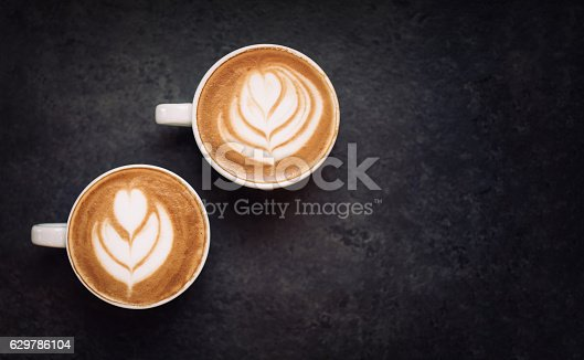 istock Two cups of coffee on black rustic background 629786104