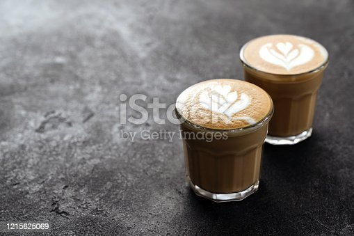 1009835562 istock photo two cups of coffee on black stone background 1215625069