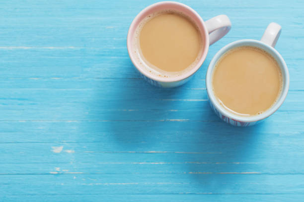 duas xícaras de café sobre fundo azul de madeira - dois objetos - fotografias e filmes do acervo