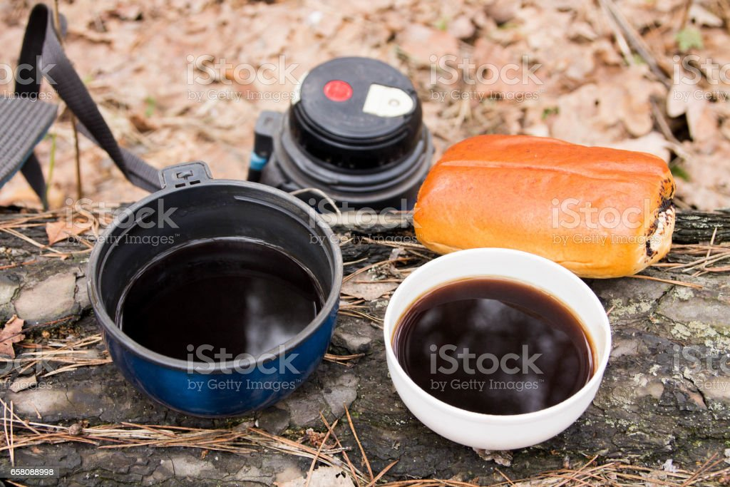 Two cups of coffee with a bun. Coffee break. Snack in the forest. royalty-free stock photo