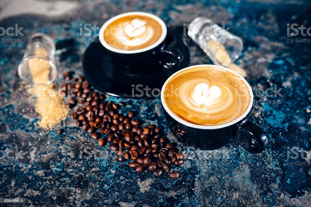 two cups of coffee with latte art. Barista pouring coffee stock photo