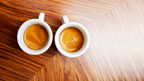 Two cups of espresso coffee on a wooden table.