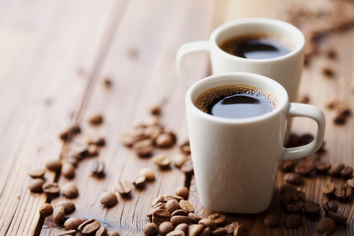 Two cups of expresso surrounded by coffee beans