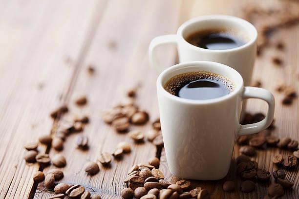 Zwei Tassen Espresso umgeben von Kaffeebohnen – Foto