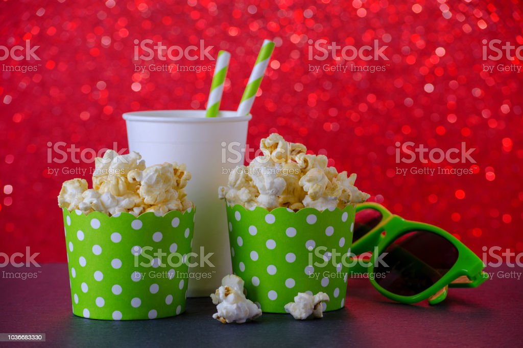 two cups of popcorn, drink and glasses for movie on red bokeh background, selective focus stock photo