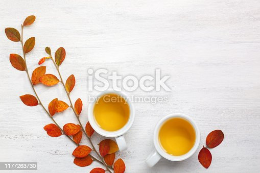 Two cups  of tea and colorful autumn leaves  on white rustic table with empty space for text or image. Flat lay.