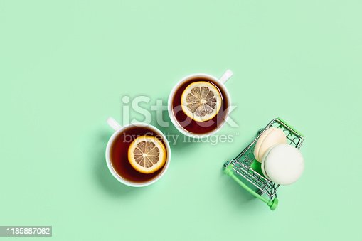 Food and drink concept. Two cups of tea with lemon and marshmallows on a food cart. Mint color. Flat lay, top view, copy space.