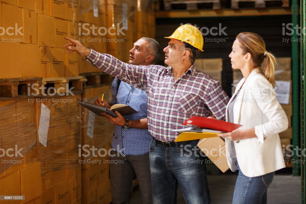 Two customs managers and warehouse worker stock photo