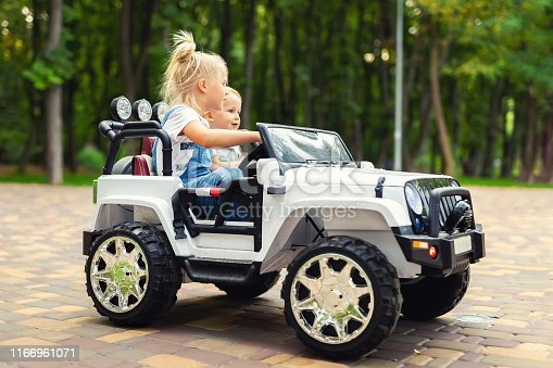 915609494istockphoto Two cute adorable blond sibings children having fun riding electric toy suv car in city park. Brother and sister enjoy playing and driving vehicle on city street outdoor. Happy childhood concept 1166961071