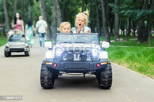 915609494istockphoto Two cute adorable blond sibings children having fun riding electric toy suv car in city park. Brother and sister enjoy playing and driving vehicle on city street outdoor. Happy childhood concept 1166961073