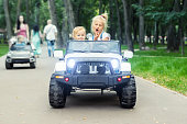 Two cute adorable blond sibings children having fun riding electric toy suv car in city park. Brother and sister enjoy playing and driving vehicle on city street outdoor. Happy childhood concept.