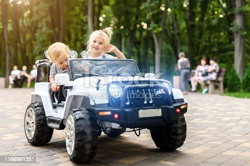 915609494istockphoto Two cute adorable blond sibings children having fun riding electric toy suv car in city park. Brother and sister enjoy playing and driving vehicle on city street outdoor. Happy childhood concept 1166961351