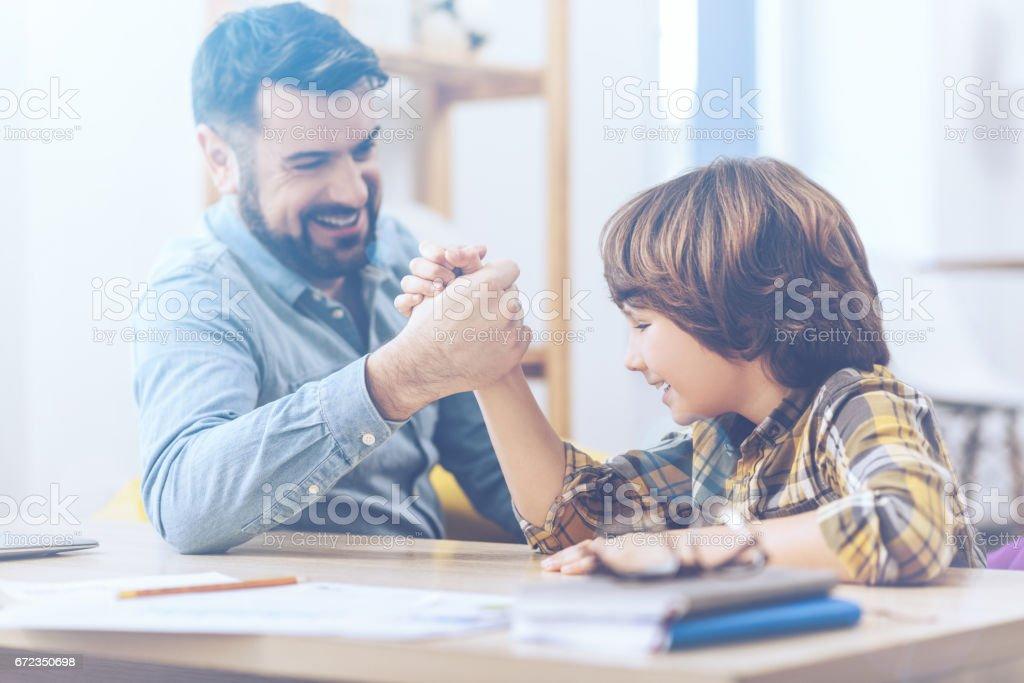 Two cute arm-wrestlers having fun stock photo