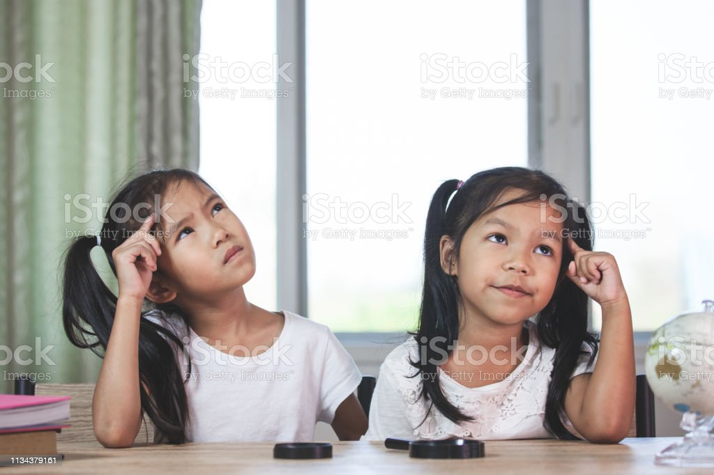 Two cute asian child girls thinking when doing homework in the room...
