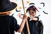 istock Two cute asian child girls wearing halloween costumes and makeup having fun on Halloween celebration together 1170811223
