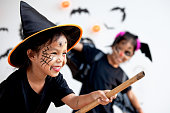 istock Two cute asian child girls wearing halloween costumes and makeup having fun on Halloween celebration together 1170811230
