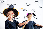 istock Two cute asian child girls wearing halloween costumes and makeup having fun on Halloween celebration together 1170811234