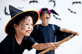 istock Two cute asian child girls wearing halloween costumes and makeup having fun on Halloween celebration together 1170811253