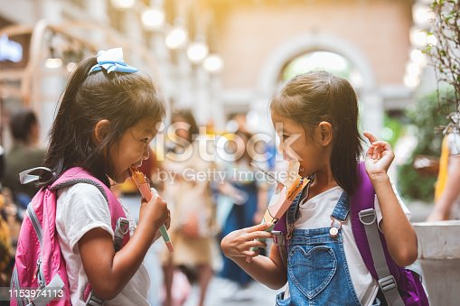 Two cute asian child girls with backpack eating pancake together after school in the school