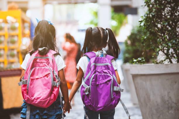 Zwei süße asiatische Kind Mädchen mit Schultasche halten Hand und gehen zusammen in der Schule – Foto