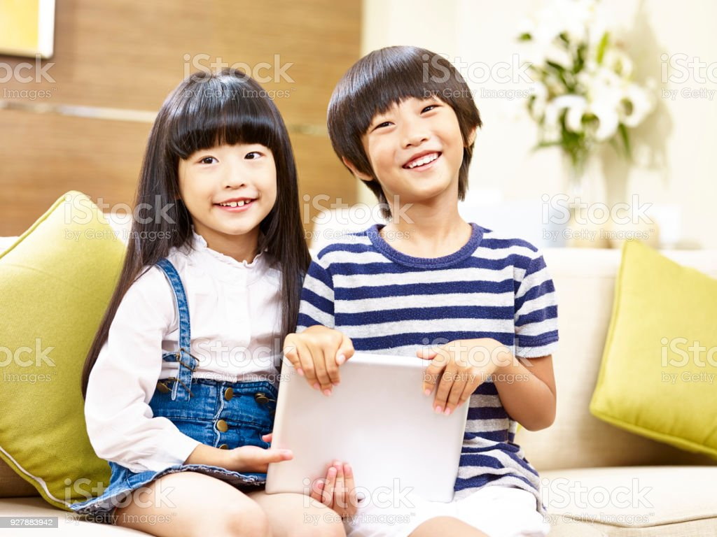 two cute asian kids sitting on couch looking at camera smiling stock