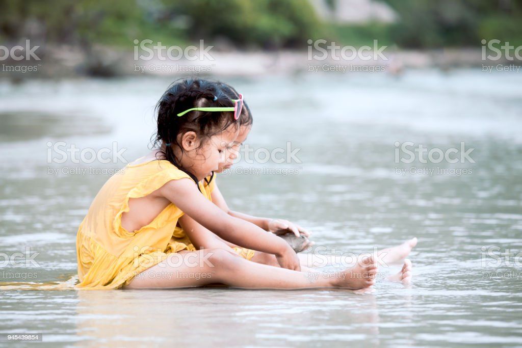 Two cute asian little child girls sitting and playing with sand on the beach together stock photo