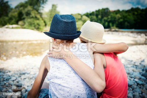 585604690istockphoto Two cute blond children, boy and girl on river bank 1169867462