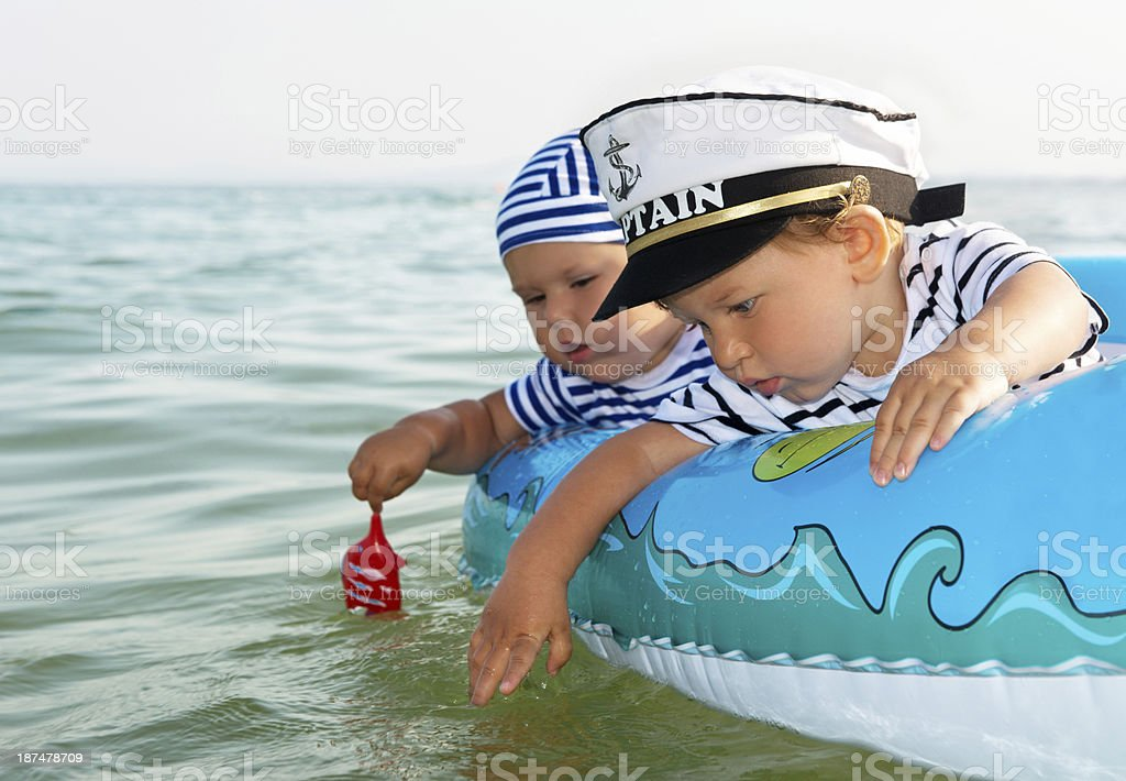 Two cute children in a inflatable boat stock photo