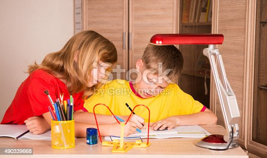 istock Two cute children working on their homework together. 490339668