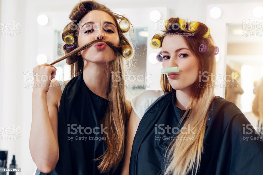 Two cute girlfriends in black cape wearing curlers making moustache out of their hair and roller in hairdressing salon royalty-free stock photo