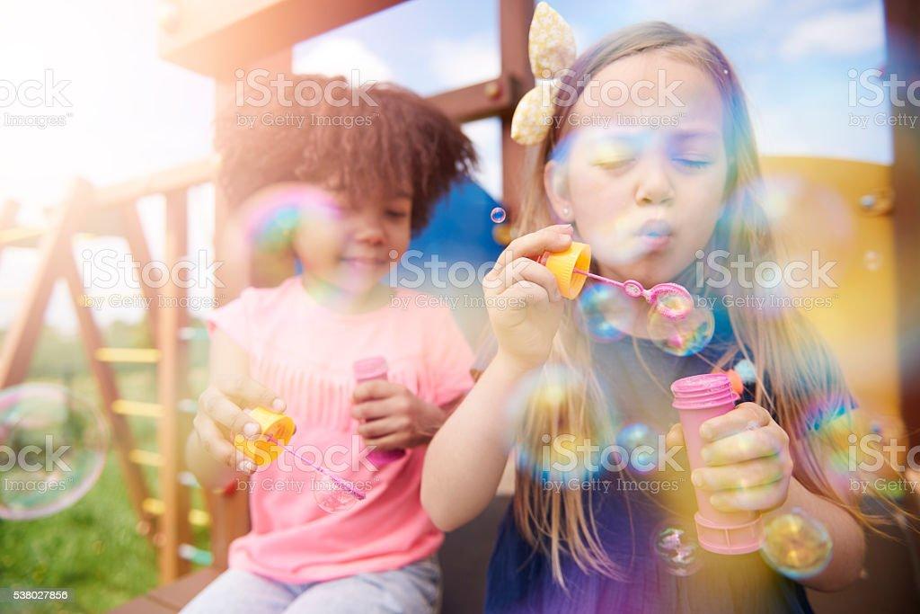 Duas lindas meninas soprando bolhas de sabão no - foto de acervo