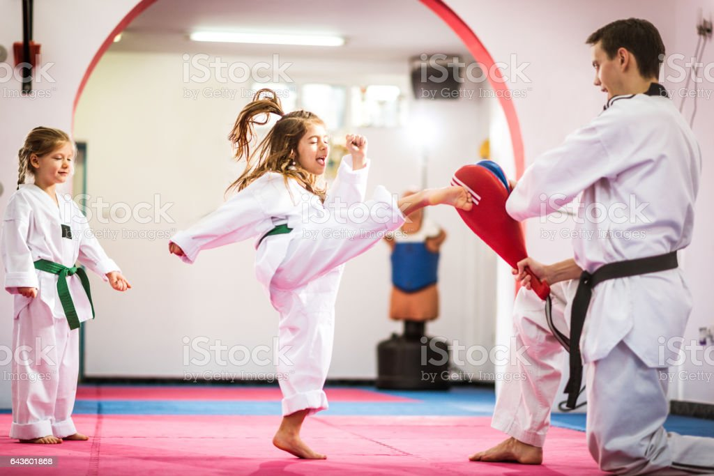 Two cute girls on taekwondo training, kicking and learning self-defence stock photo