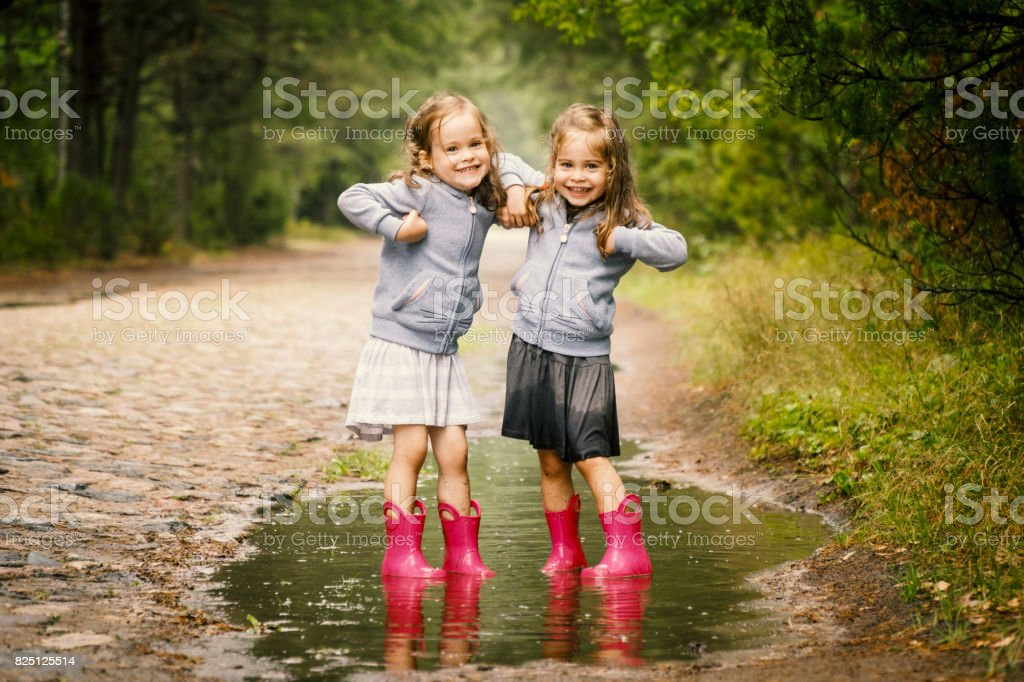 Two cute girls play in the puddle stock photo
