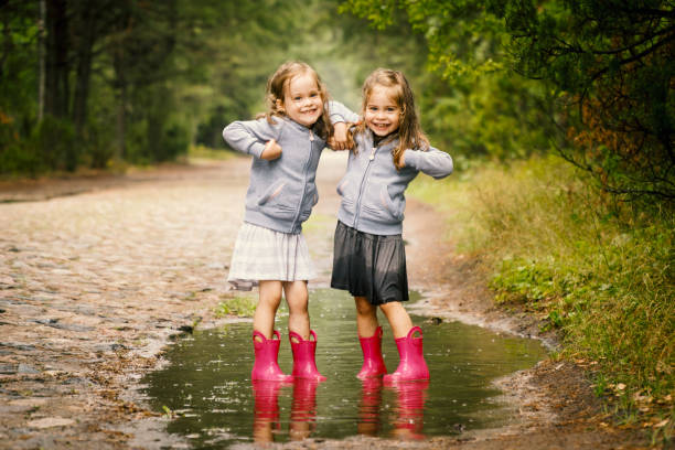Two cute girls play in the puddle