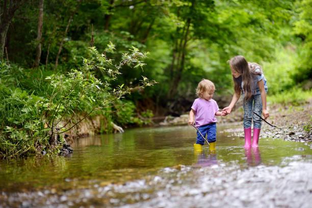 twee schattige meisjes spelen in het bos. - bos spelen stockfoto's en -beelden