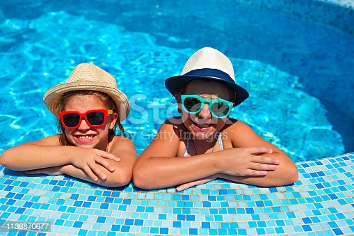 Two cute girls wearing sunglasses and hats in swimming pool. Summer vacation and travel concept